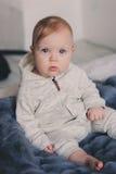 Retrato del bebé de 8 meses lindo que se sienta en la cama en la manta hecha punto Imagenes de archivo