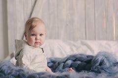 Retrato del bebé de 8 meses lindo que se sienta en la cama en la manta hecha punto Fotos de archivo