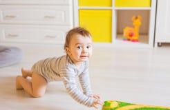 Retrato del bebé divertido de arrastre dentro en casa Foto de archivo