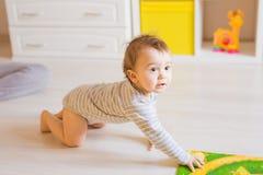 Retrato del bebé divertido de arrastre dentro en casa Fotografía de archivo