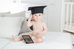 Retrato del bebé divertido en casquillo de la graduación usando la tableta digital Foto de archivo