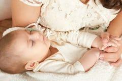 Retrato del bebé el dormir en mano de la madre, maternidad feliz y concepto de la niñez Imagen de archivo libre de regalías