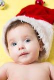 Retrato del bebé en un sombrero rojo de Papá Noel con las bolas en el árbol del Año Nuevo Pequeño hermoso celebra la Navidad holi Imágenes de archivo libres de regalías