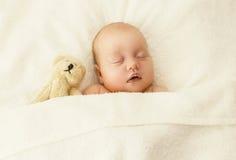 Retrato del bebé lindo que duerme así como el juguete del oso de peluche Imagen de archivo libre de regalías