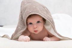 Retrato del bebé o de la muchacha desnudo dulce con la toalla en la cabeza que mira inocente de impresión sobre algo y Fotos de archivo