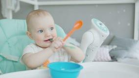 Retrato del bebé que se sienta en el highchair con la cuchara metrajes