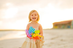Retrato del bebé sonriente con el juguete del molino de viento Foto de archivo