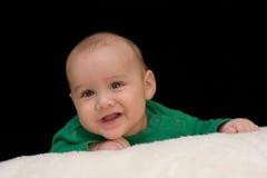 Retrato del bebé sonriente en verde Imagen de archivo