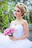 Retrato del blonde atractivo hermoso de la novia en un vestido blanco con la PU Fotografía de archivo