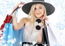 Retrato del blonde en sombrero con los bolsos de compras Fotografía de archivo libre de regalías