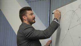 Retrato del busiessman que está escribiendo la situación del mercado digital de moneda en el whiteboard en conferencia almacen de video