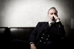 Retrato del caballero adulto que lleva el traje de moda y que sienta el estudio moderno en el sofá de cuero contra el hormigón va Imagen de archivo