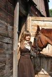 Retrato del caballo del adolescente y de la castaña cerca de la puñalada de madera Imagenes de archivo