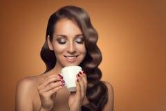 Retrato del café de consumición de la mujer hermosa en fondo marrón Fotografía de archivo