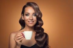 Retrato del café de consumición de la mujer hermosa en fondo marrón Foto de archivo