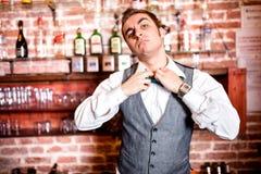 Retrato del camarero enojado y subrayado con el bowtie detrás de la barra Foto de archivo