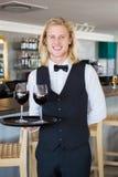 Retrato del camarero que sostiene la bandeja con los vidrios de vino rojo Fotos de archivo