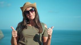 Retrato del caminante de la mujer en sombrero y gafas de sol que goza del sol que aumenta las manos que consiguen los pulgares gr almacen de video
