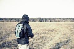 Retrato del caminante de los hombres en el campo con la mochila y los polos Imagen de archivo