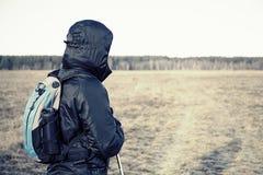 Retrato del caminante de los hombres en el campo con la mochila y los polos Imagen de archivo libre de regalías