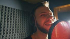 Retrato del cantante joven que canta en estudio de los sonidos Hombre hermoso que registra emocionalmente la nueva canción El ind almacen de video