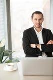 Retrato del CEO que se sienta en el escritorio con los brazos cruzados imagenes de archivo