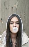 Retrato del chicle de globo de la chica joven que sopla Imagen de archivo libre de regalías