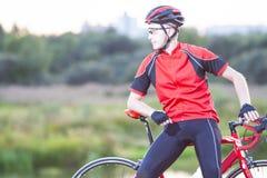 Retrato del ciclista caucásico que se relaja al aire libre en fondo de la naturaleza Fotos de archivo libres de regalías