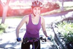 Retrato del ciclista femenino que completa un ciclo en campo el día soleado Foto de archivo libre de regalías