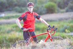 Retrato del ciclista del hombre con la bicicleta del camino que presenta al aire libre Fotos de archivo