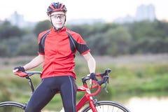 Retrato del ciclista del hombre que se relaja con la bicicleta del camino al aire libre Imagen de archivo