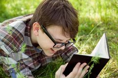 Retrato del cierre del adolescente para arriba Muchacho con el libro y la risa de lectura de los vidrios Fin de semana feliz parq Fotografía de archivo