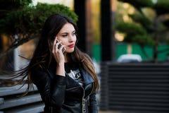 Retrato del cierre hermoso sonriente de la mujer joven para arriba con el teléfono móvil, contra la calle del verde del verano de Foto de archivo