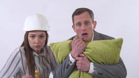 Retrato del cierre loco de los pares para arriba El hombre sostiene la almohada, mujer en el baile del casco del constructor con  almacen de video