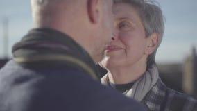 Retrato del cierre mayor de la cara de la mujer cerca de la cara del hombre mayor Los pares mayores hablan el uno al otro y miran almacen de video