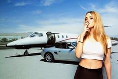 Retrato del cigarrillo que fuma de la mujer joven con el coche y el aeroplano en el fondo Foto de archivo libre de regalías