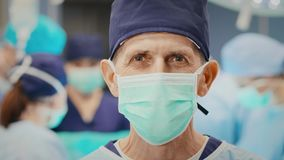 Retrato del cirujano maduro en la sala de operaciones almacen de metraje de vídeo