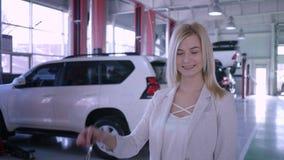 Retrato del cliente feliz femenino con llaves del coche después de la reparación profesional en la gasolinera almacen de metraje de vídeo