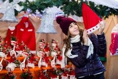 Retrato del cliente femenino cerca del contador con los regalos de la Navidad Imagen de archivo