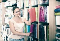 Retrato del cliente femenino que elige manteles en la materia textil casera Fotografía de archivo libre de regalías