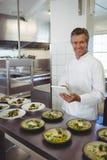 Retrato del cocinero de sexo masculino que usa la tableta digital en la estación de la orden Imagenes de archivo