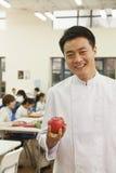 Retrato del cocinero en la cafetería de la escuela que sostiene la manzana fotos de archivo libres de regalías