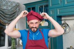 Retrato del cocinero en sombrero y del delantal en la cocina Hombre en uniforme de la cocina foto de archivo