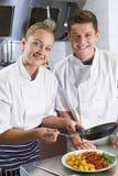 Retrato del cocinero Instructing Female Trainee en el restaurante Kitche foto de archivo libre de regalías