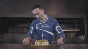Retrato del cocinero que demuestra apenas el plato sabroso acabado en cierre moderno del restaurante del pavo para arriba Hombre  almacen de video