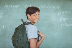 Retrato del colegial con la mochila que se opone a la pizarra en sala de clase Imagen de archivo