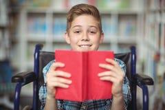 Retrato del colegial discapacitado que sostiene el libro en biblioteca Fotografía de archivo