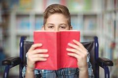 Retrato del colegial discapacitado que sostiene el libro en biblioteca Foto de archivo