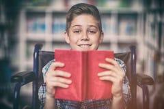 Retrato del colegial discapacitado que sostiene el libro en biblioteca Imagen de archivo libre de regalías