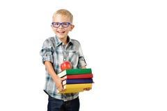 Retrato del colegial divertido con los libros y de la manzana aislada en el fondo blanco Educación Imagenes de archivo